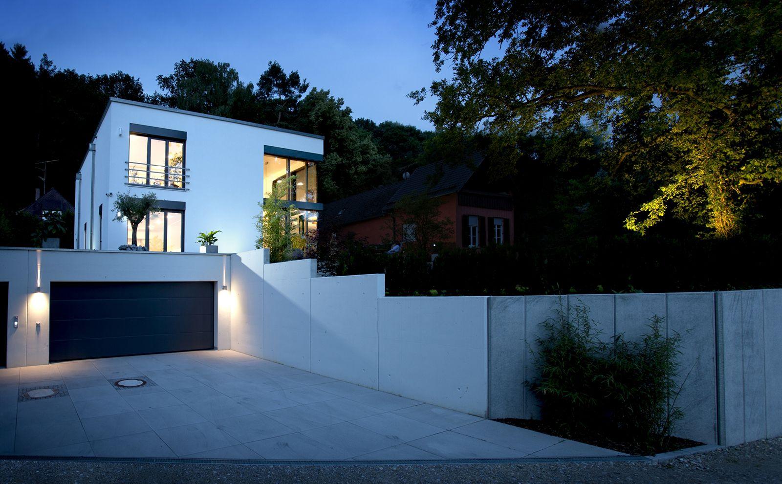 Weißes Haus in Würfeloptik am Waldrand im Dunkeln