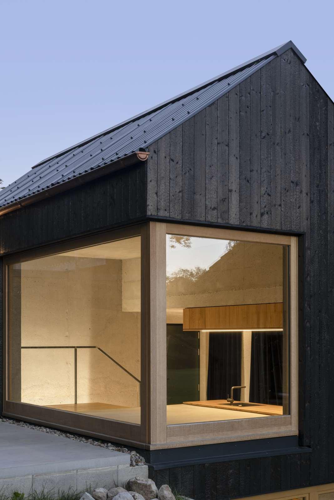 Kleine Haus mit Holzfassade und Pivot-Fenster