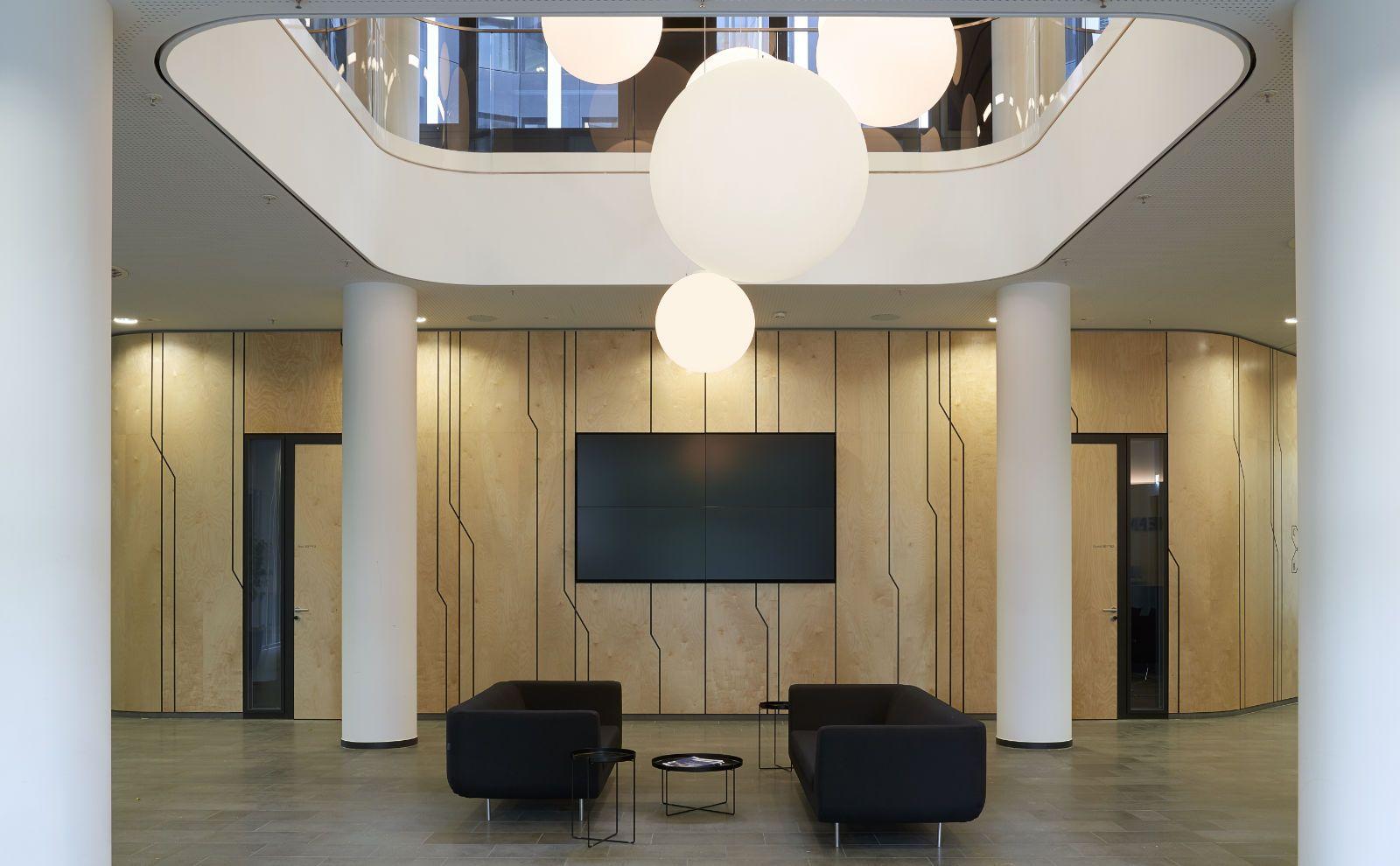 Innenhof der DB Schenker Unternehmenszentrale von BAID Architektur mit Sofa und Holzwand