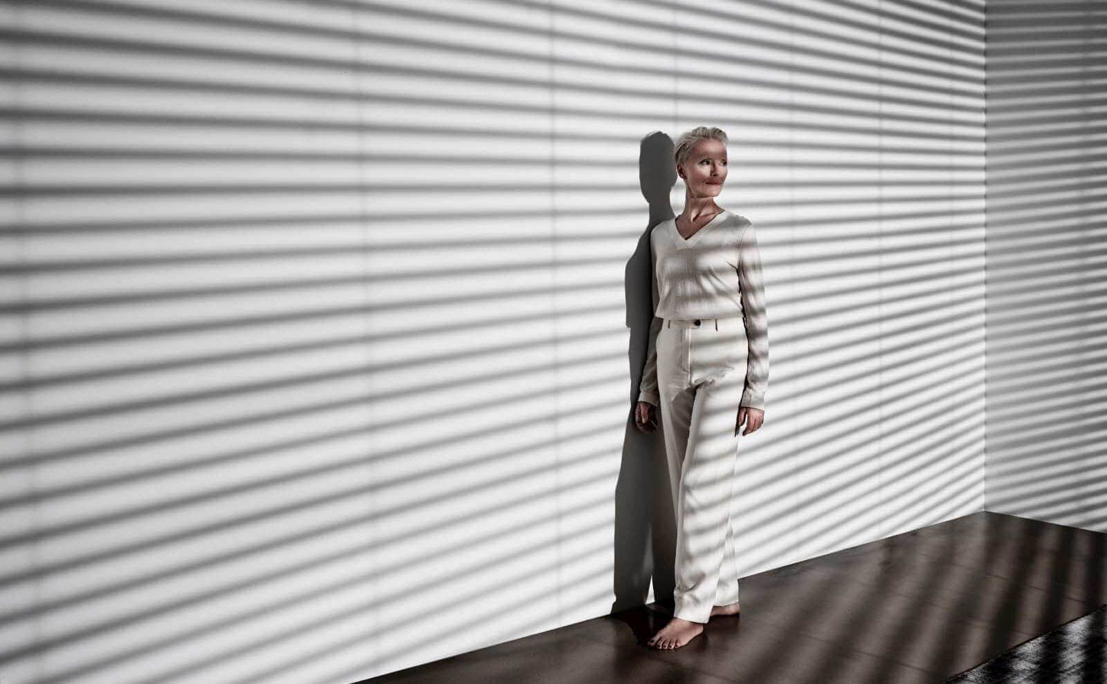 Frau im Zimmer mit Schatten von Jalousie