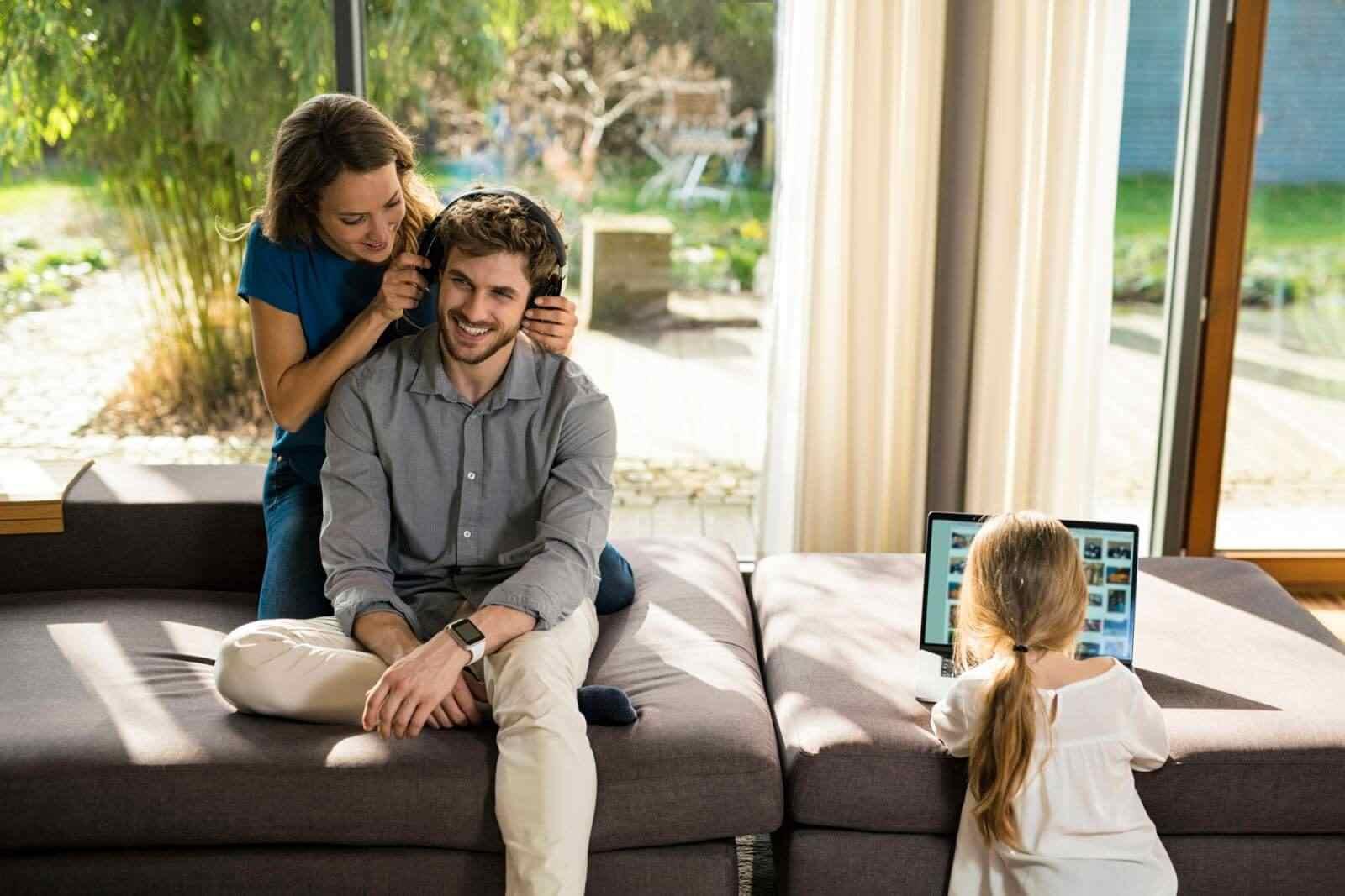 Eltern mit Technik und Kind im Wohnzimmer