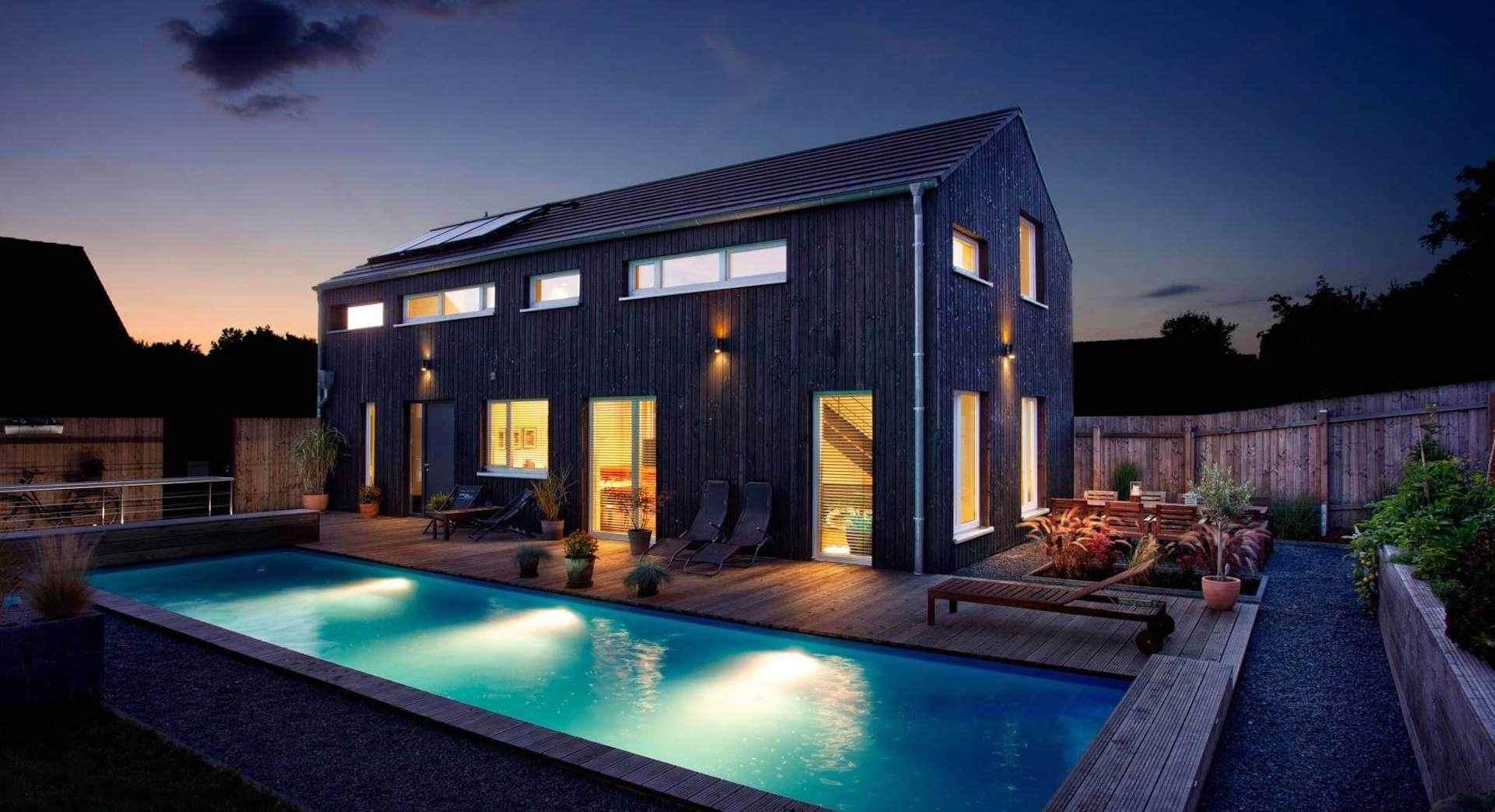 Beleuchtetes Holzhaus im Dunkeln mit Pool