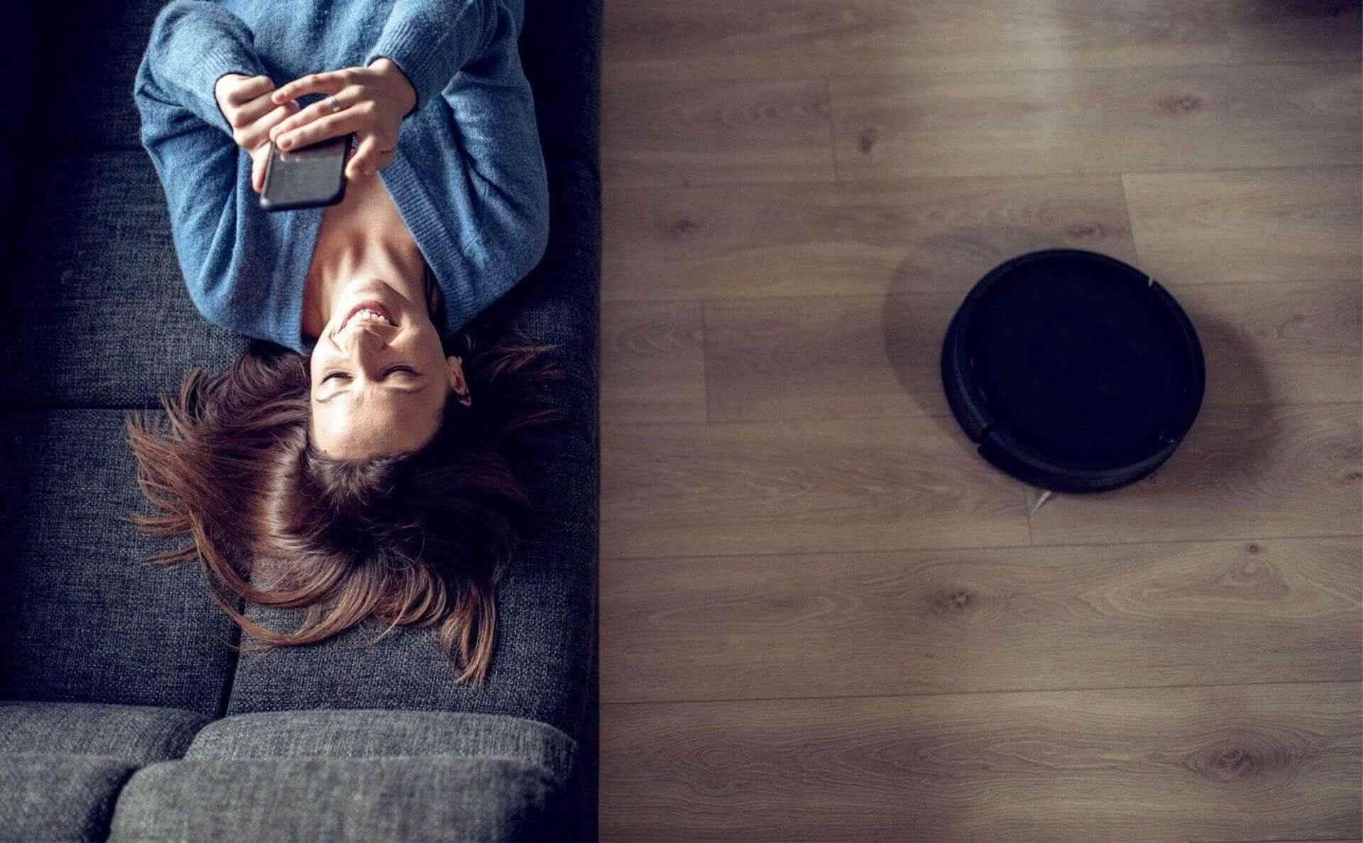 Frau mit Smartphone und Saugroboter