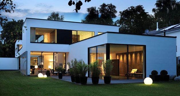Modernes Atrium-Haus mit weißer Außenfassade und schwarzen Fenstern