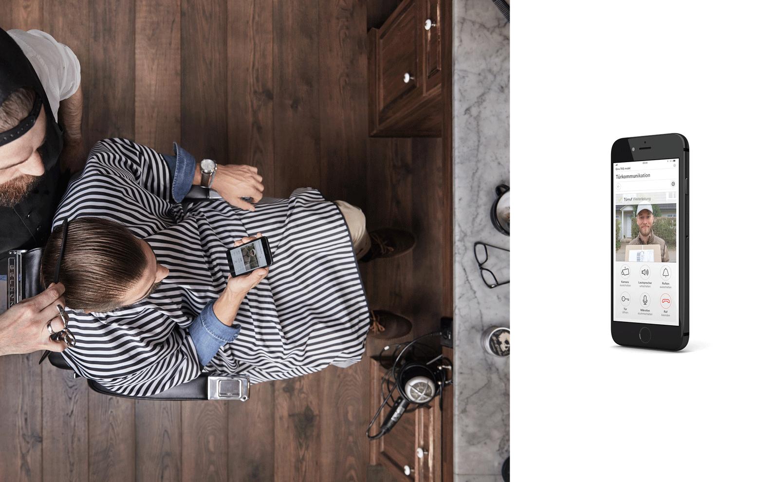 Frau sitzt im Barbershop und sieht auf dem Handy wer vor wer ihrer Haustür steht, mit Produkt-Freisteller