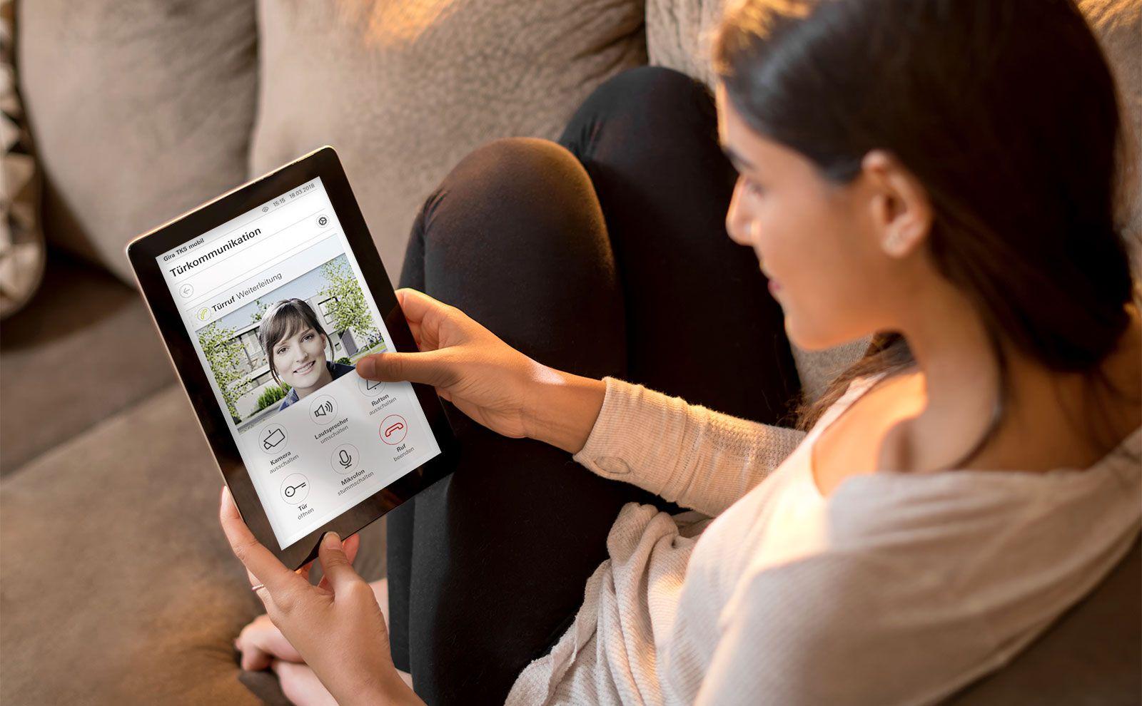 Frau hält Tablet mit Smart Home App-Anzeige Tuerkommunikation