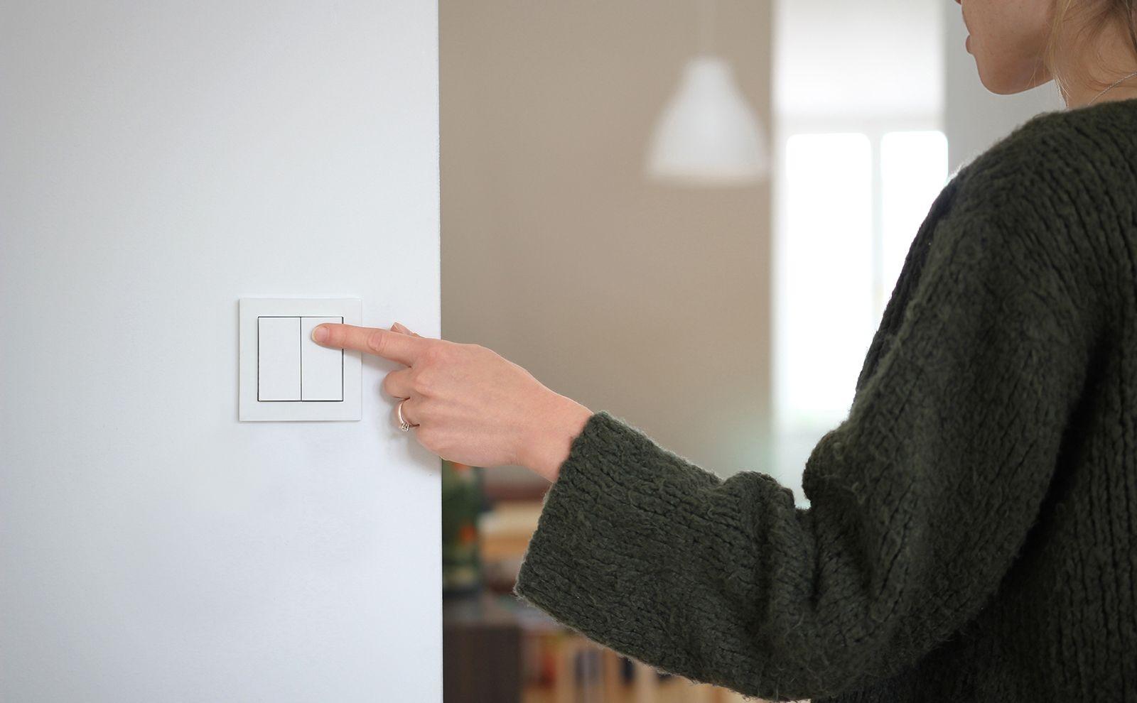 Frau drückt Friends of Hue-Schalter an der Wand