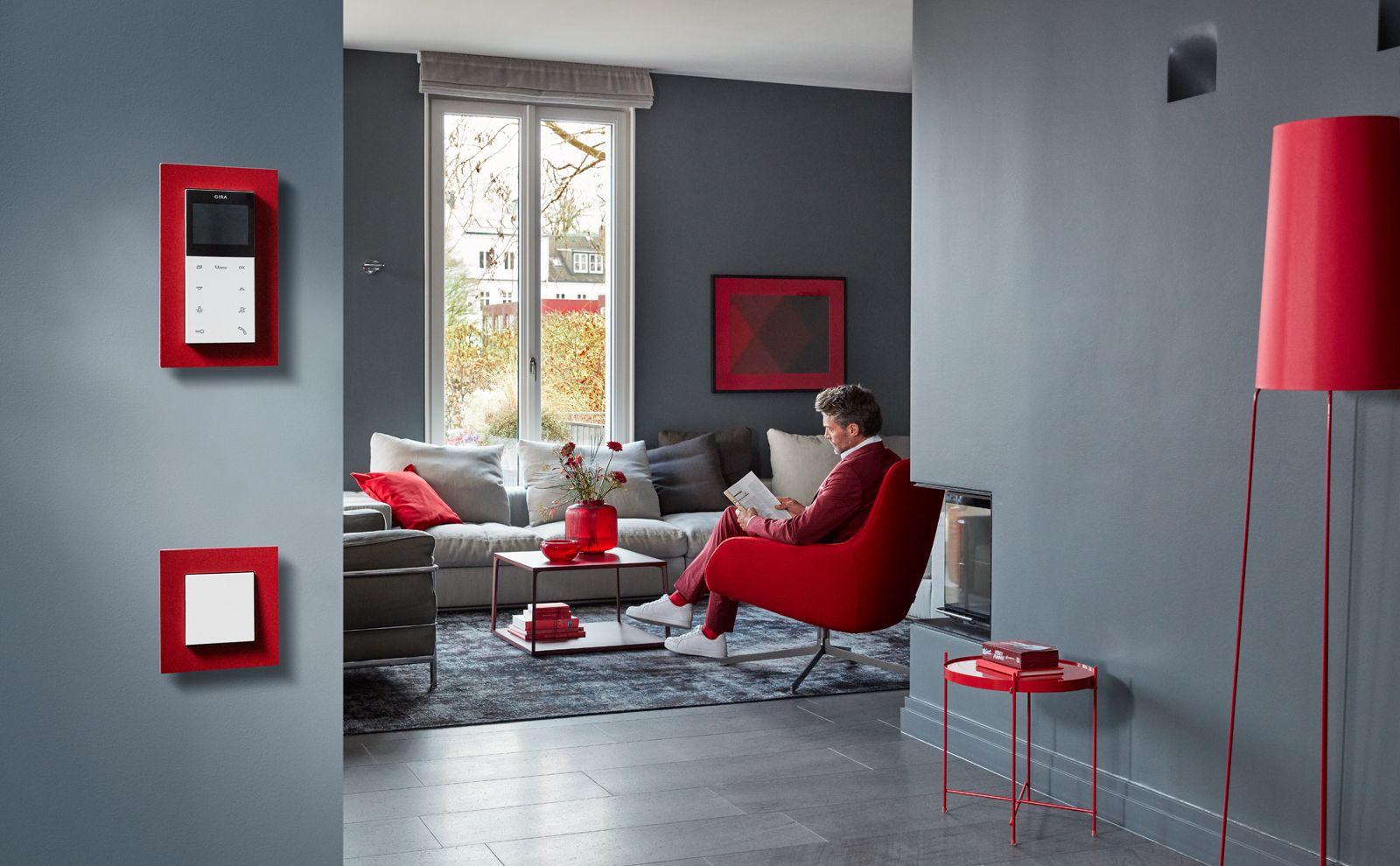 Mann in einem Wohnzimmer mit Türsprechanlage AP und Gira Schalter