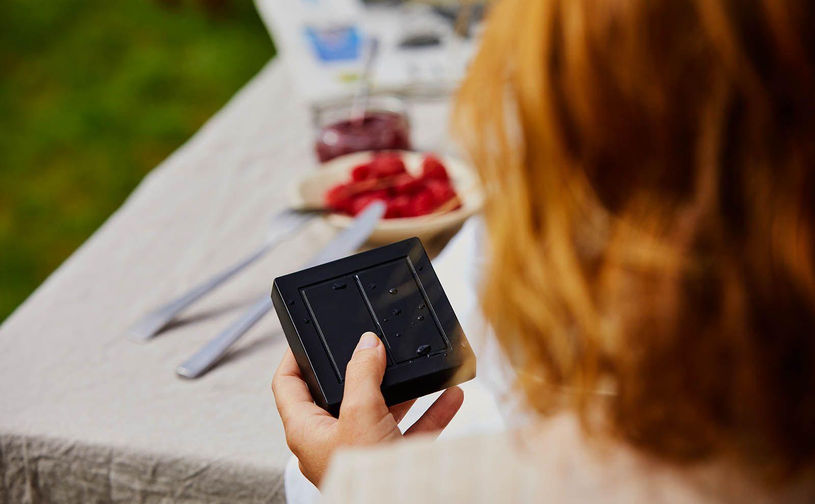 Gira Senic mobiler Schalter in der Hand